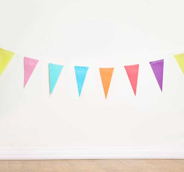 birthday decoration flags on a plain white wall - happy birthday banner stock photos and pictures