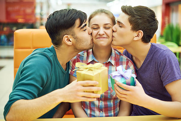 Birthday double kiss Happy girl getting double kiss from her male friends group of friends giving gifts to the birthday girl stock pictures, royalty-free photos & images