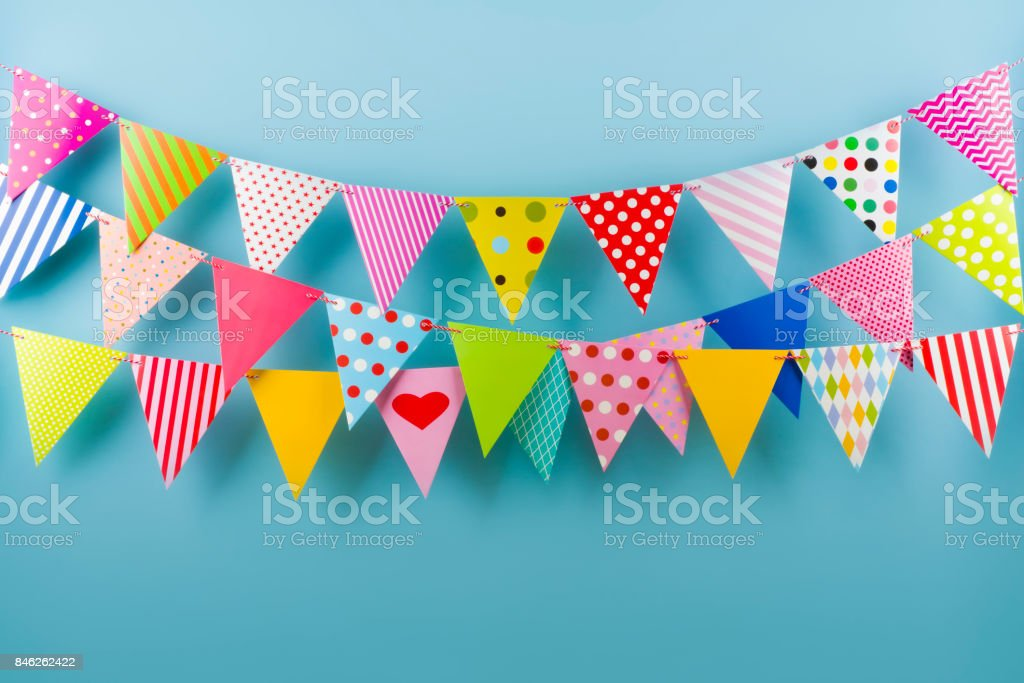 Birthday fest garlands from colorful triangular flags on blue background stock photo