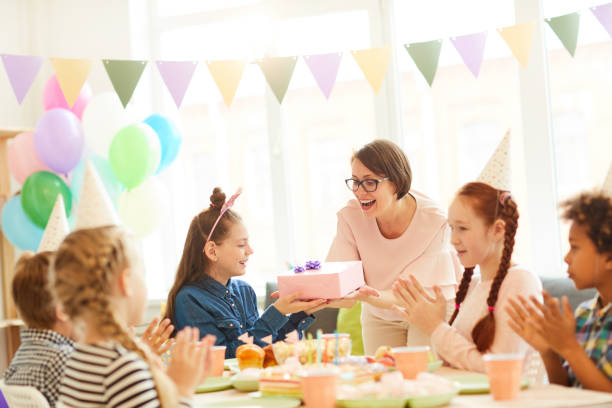 Birthday Girl getting Presents Portrait of excited little girl  receiving gifts during Birthday party with friends, copy space group of friends giving gifts to the birthday girl stock pictures, royalty-free photos & images