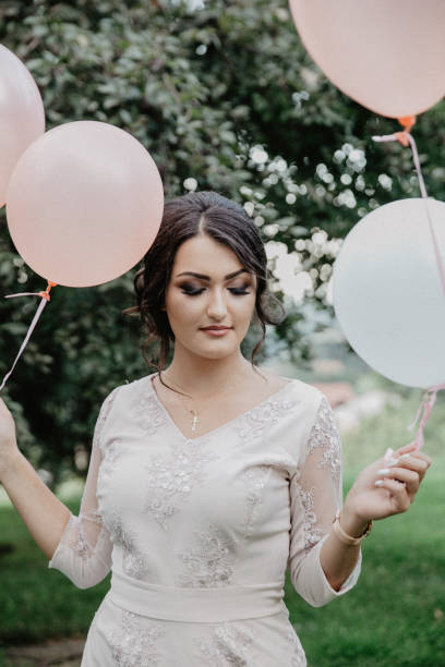 Birthday girl holding balloons in the park. stock photo