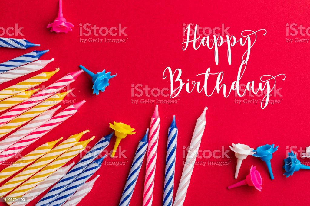 Birthday greeting card. With very colorful candles on a red...