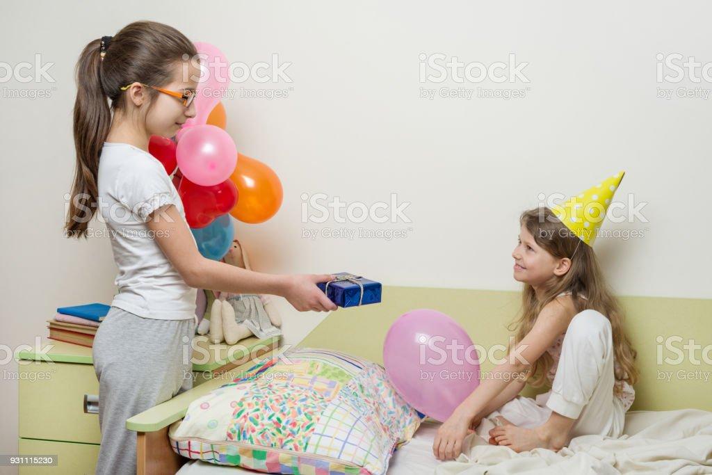 Doğum günü sabah. Sevimli küçük kız kardeşi için sürpriz hediye vererek ablası. Çocuklar evde yatakta - Royalty-free 13 - 19 Yaş arası Stok görsel