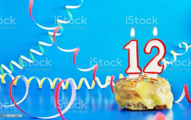 Birthday of twelve years cupcake with white burning candle in the of picture id1139382733?b=1&k=6&m=1139382733&s=612x612&h=p7p2y6au1d6yn3w5zfmpgtxrys ahzxyes6gbrsjsr8=