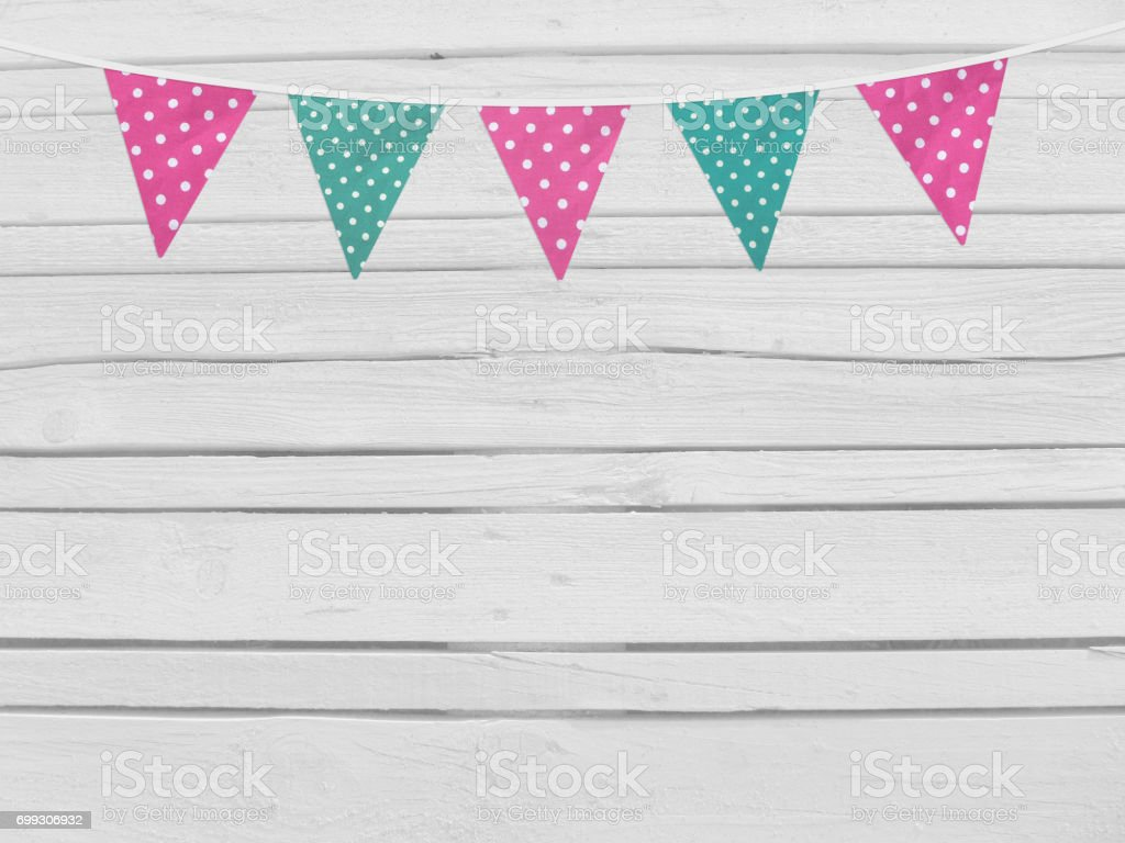 Birthday or baby shower mockup scene. String of pink and mint dotted fabric flags. Party decoration. Old white wooden background, empty space. Top view stock photo