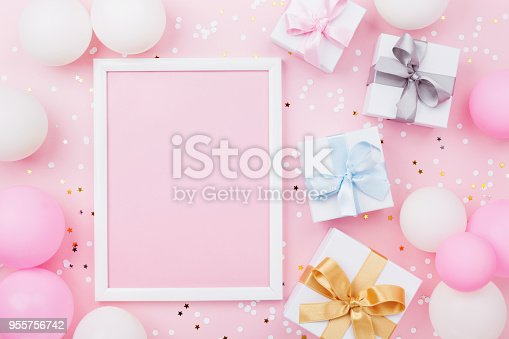 istock Birthday or holiday mockup with frame, gift box, pastel balloons and confetti on pink table top view. Flat lay. 955756742