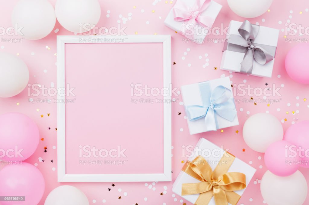Birthday or holiday mockup with frame, gift box, pastel balloons and confetti on pink table top view. Flat lay. stock photo