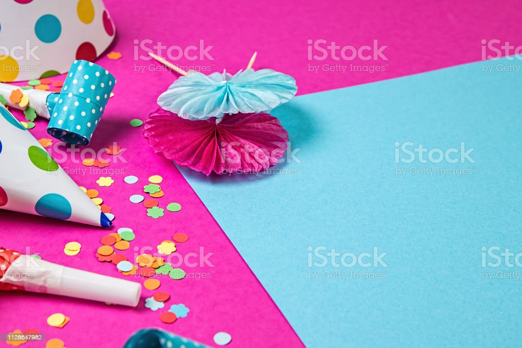 Birthday paper caps with candles, confetti and straws on blue...