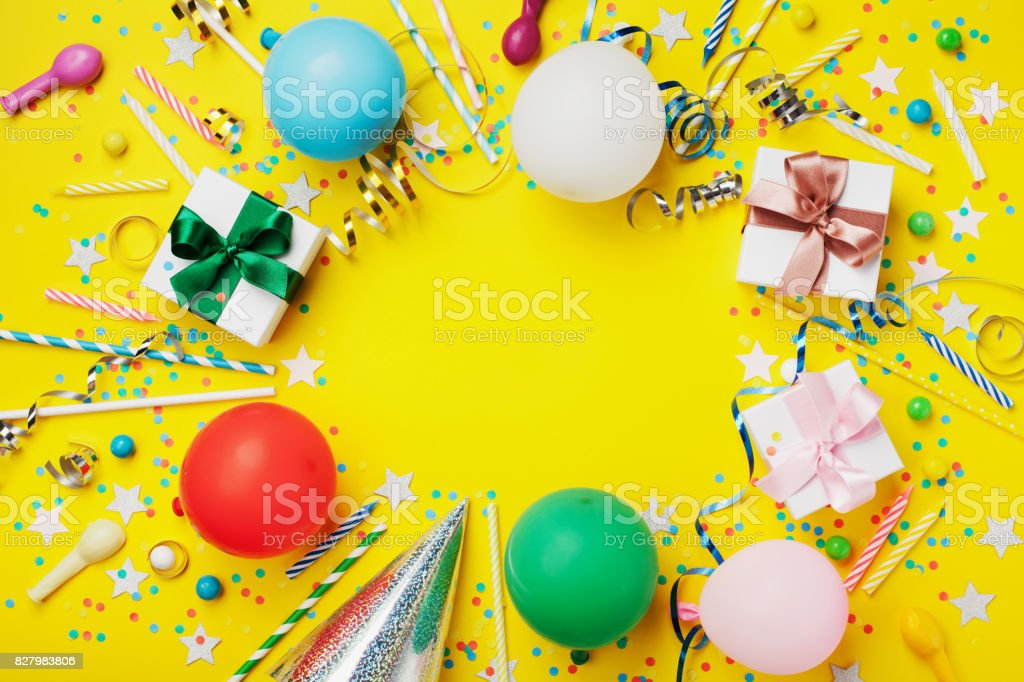 Birthday party background or frame with colorful balloon, gift, confetti, silver star, carnival cap, candy and streamer. Holiday flyer with space for text. stock photo