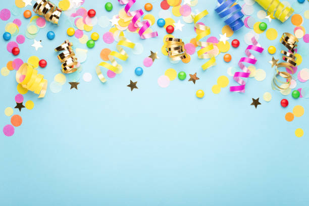 Birthday party background. Birthday party background on blue. Top view. Border made of colorful serpentine, candies and confetti. celebration stock pictures, royalty-free photos & images