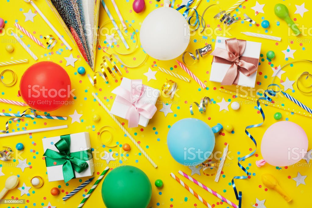 Birthday party background with balloon, gift, confetti, carnival cap, star, candy and streamer. Colorful children greeting card. stock photo