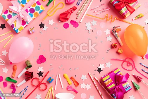950793576 istock photo Birthday party background with party gifts, candles and balloons with copy space top view on pink background 1254097953