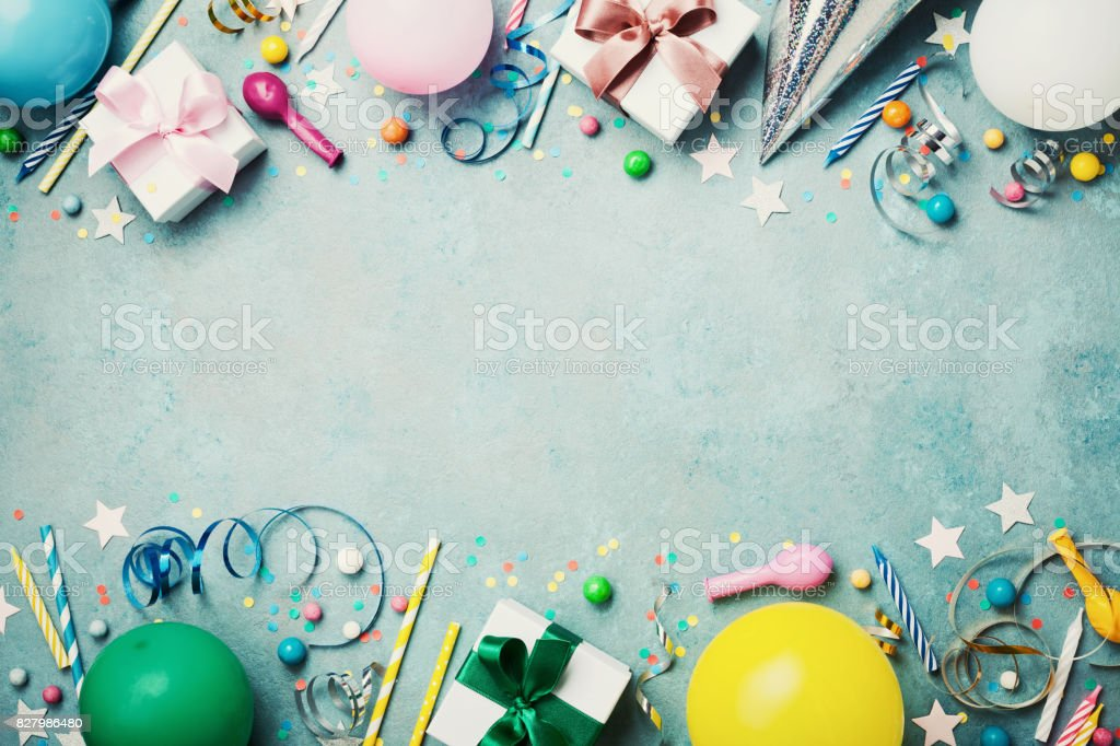 Birthday party banner or background with colorful balloon, gift, carnival cap, confetti, candy and streamer. Flat lay style. Space for greeting text. stock photo