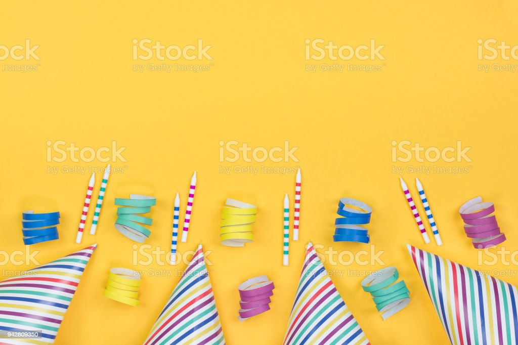 Birthday party composition on yellow background. Top view with copy...
