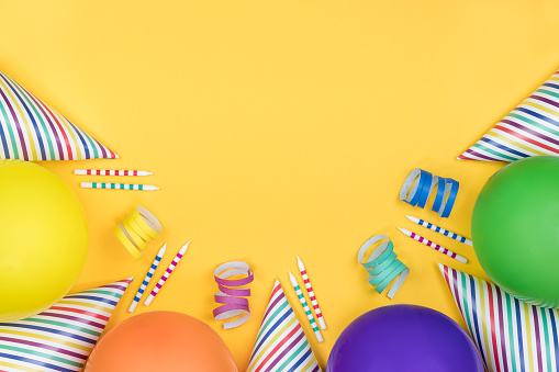Birthday party composition on yellow background. Top view with copy space.