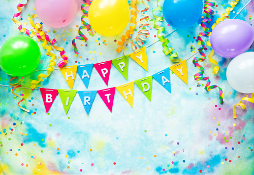 Party frame with balloons, streamers and confetti on colorful background with copy space and text Happy Birthday