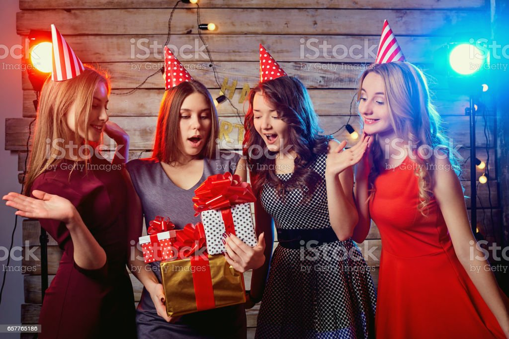 Birthday party girlfriends girls. Yong woman in hats with presen stock photo