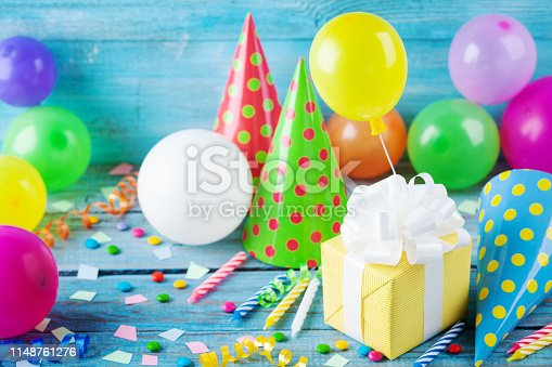 Birthday party background with gift or present box, colorful balloons, confetti, carnival cap and streamer. Holiday supplies on blue table.