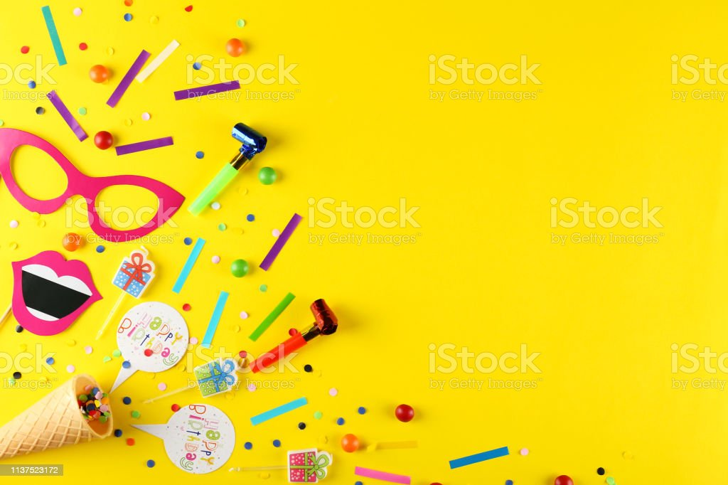 Photo booth props and party horns on yellow background. Paper...