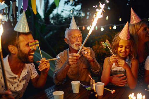 Multi generation family on birthday party in back yard. Wearing birthday hats, holding sparklers  and having fun together, with birthday cake in front of them.