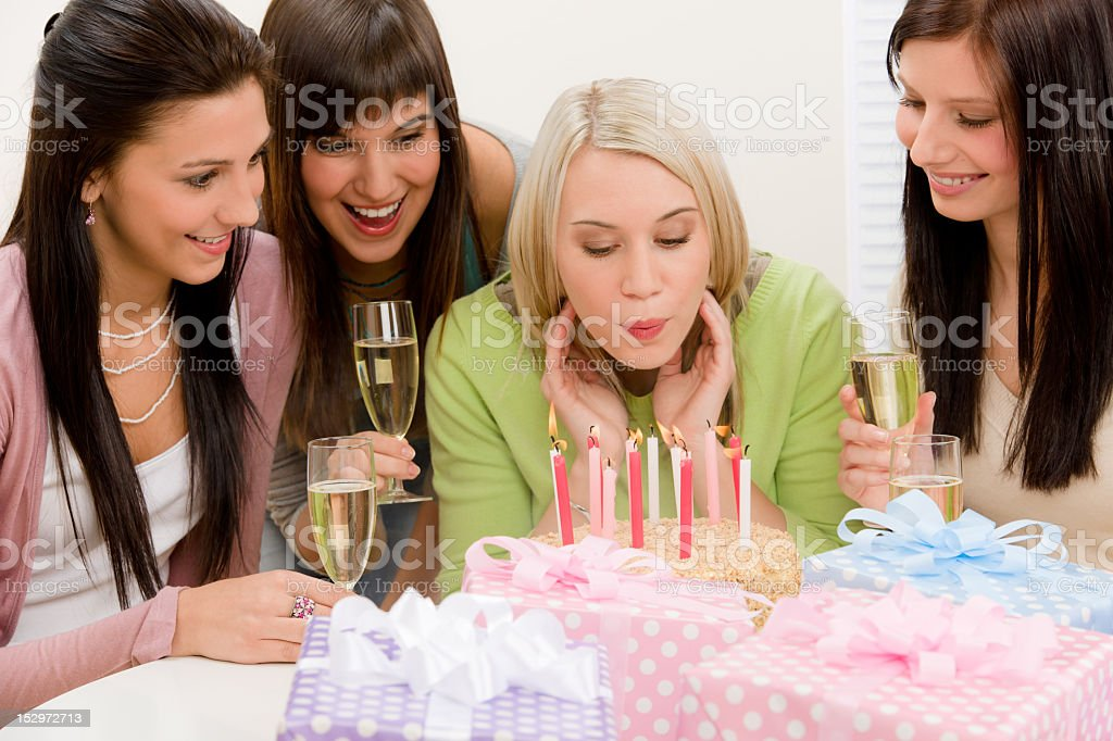 Birthday party - woman blowing candle on cake royalty-free stock photo