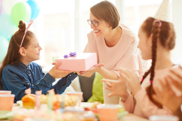 Birthday Present from Loving Mom Portrait of happy girl  receiving gift from mom during Birthday party with friends, copy space group of friends giving gifts to the birthday girl stock pictures, royalty-free photos & images