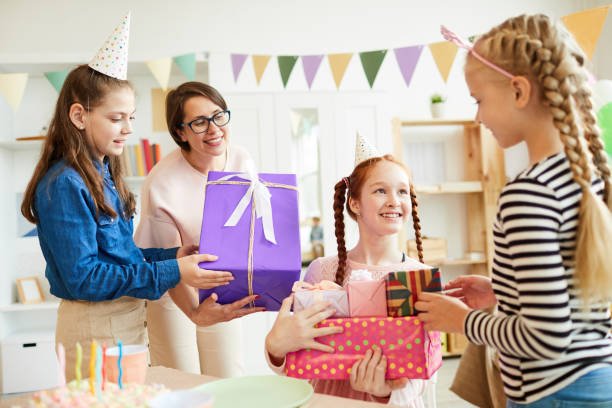 Birthday Presents Portrait of happy red haired  girl receiving gifts from friends during Birthday party, copy space group of friends giving gifts to the birthday girl stock pictures, royalty-free photos & images