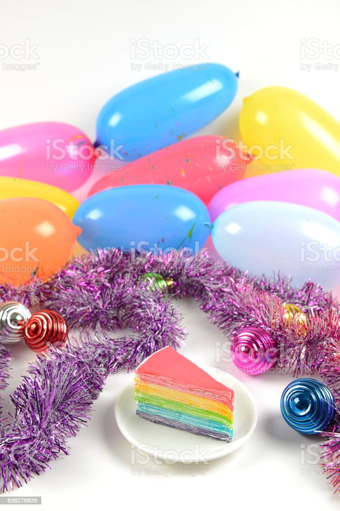 Birthday rainbow cake on party balloons background. stock photo
