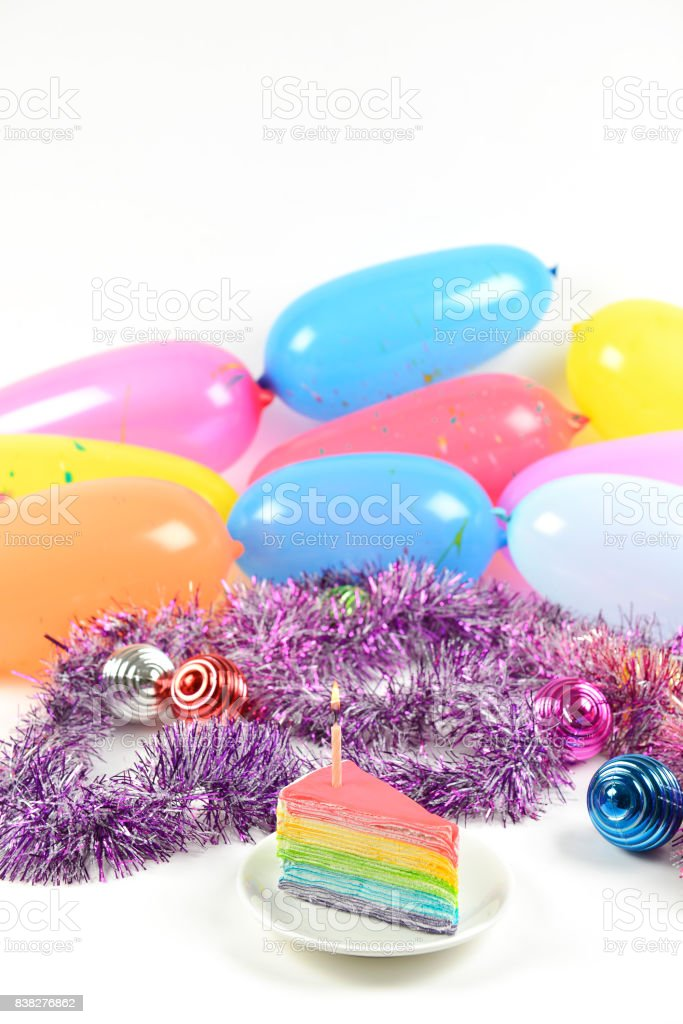 Birthday rainbow cake with candle on party balloons background. stock photo