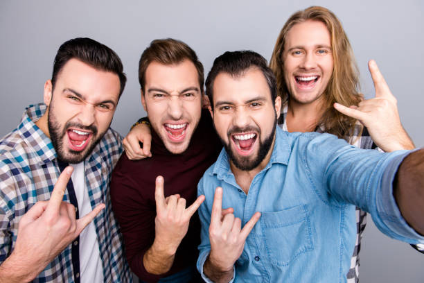 birthday rock and roll leisure music playing band hobby trip concept. four mad virile masculine brutal handsome bearded excited guys gesturing horns, casual checkered outfit isolated gray background - concert selfie stock photos and pictures