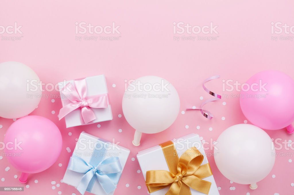 Birthday table with pastel balloons, gift or present box and confetti top view. Flat lay. - Stock image .