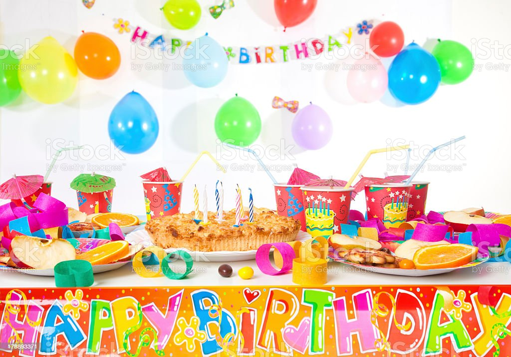 A birthday table with plates, cups, decorations, and cake stock photo