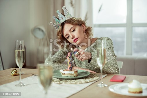 istock Birthday woman lightning the candle on birthday cake staying alone 1136220856