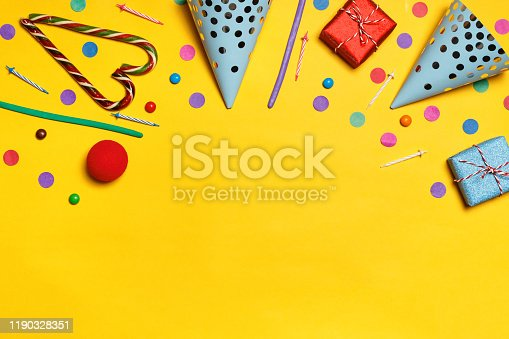 1093222958 istock photo Birthday yellow background with party caps presents confetti candy. Copy space 1190328351