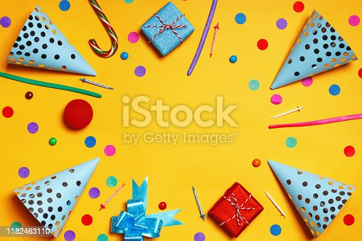 1093222958 istock photo Birthday yellow background with party hats gifts candy confetti 1182463110