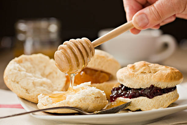 Biscuit And Honey A close up shot of a hand applying honey to a freshly baked biscuit with a wooden honey dipper. biscuit stock pictures, royalty-free photos & images