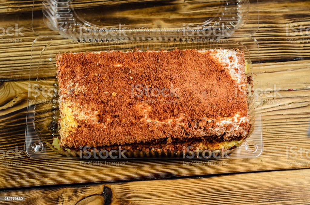 Biscuit cake in plastic container on wooden table. Top view royalty-free stock photo
