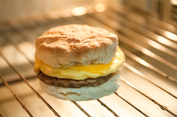 Biscuit, Sausage, egg & cheese. Breakfast sandwich cooking A breakfast sandwich. Sausage,egg and cheese. Oven inside biscuit stock pictures, royalty-free photos & images