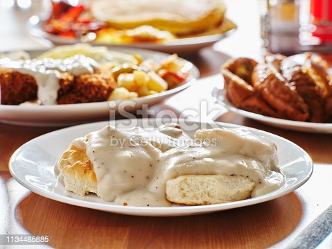 biscuits and gravy with breakfast foods on plate shot with selective focus