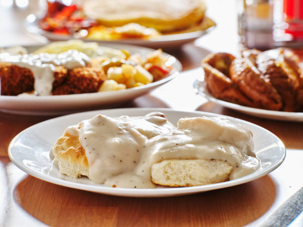 biscuits and gravy with breakfast foods on plate biscuits and gravy with breakfast foods on plate shot with selective focus biscuit stock pictures, royalty-free photos & images