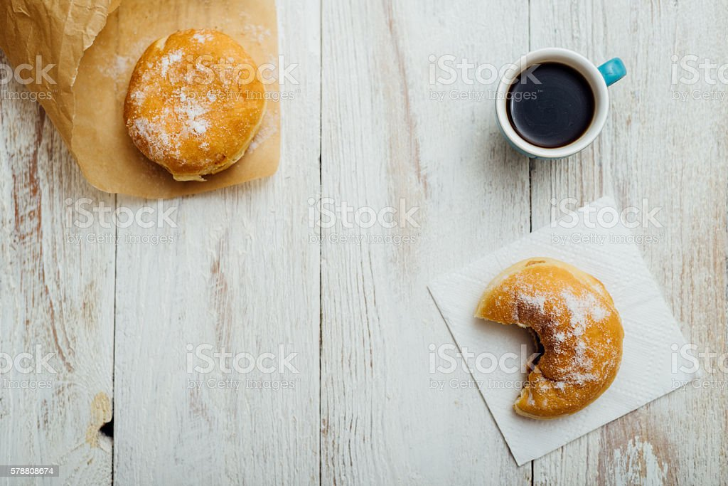 Bismarck donut on wooden table in paper stock photo
