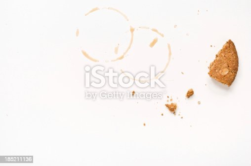 Cookie crumbs and coffee stains on white table.