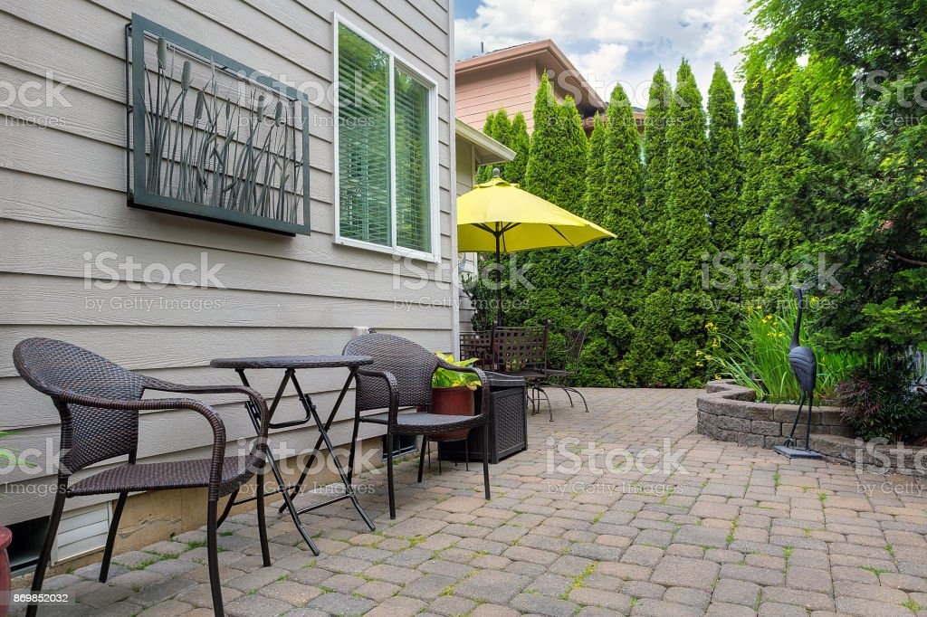 Bistro chairs and table on stone paver bricks patio in garden backyard with pond stock photo