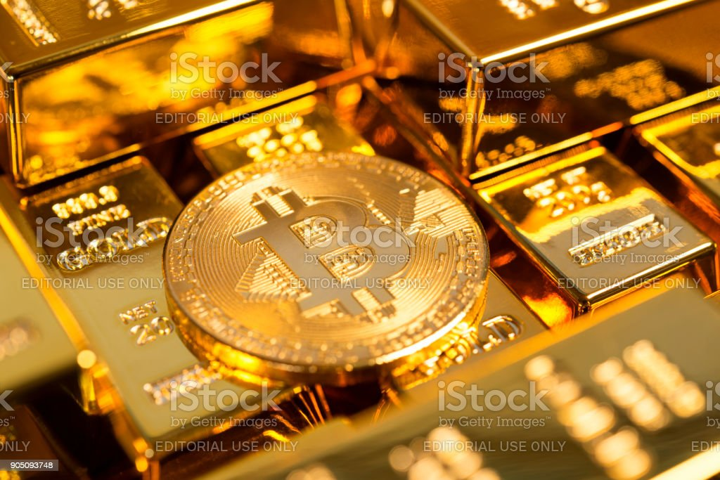 Bitcoin among gold bars stock photo