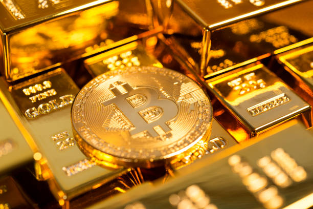 Bitcoin among gold bars stock photo