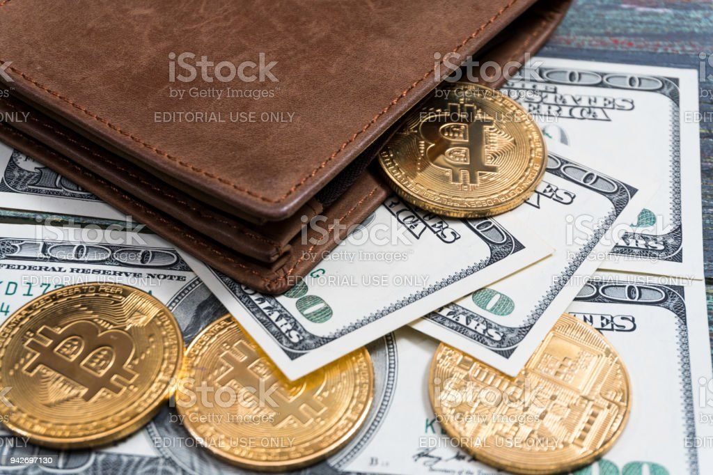 Bitcoin and money in a purse on a colored wooden background stock photo