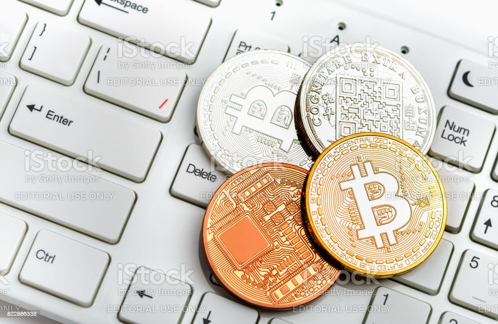 Bitcoin coin on white keyboard Moscow, Russia - July 19, 2017: Bitcoin simbol over dollar and euro background Banking Stock Photo