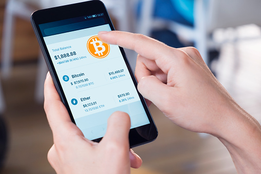 Woman using a smart phone displaying a bitcoin wallet screen.