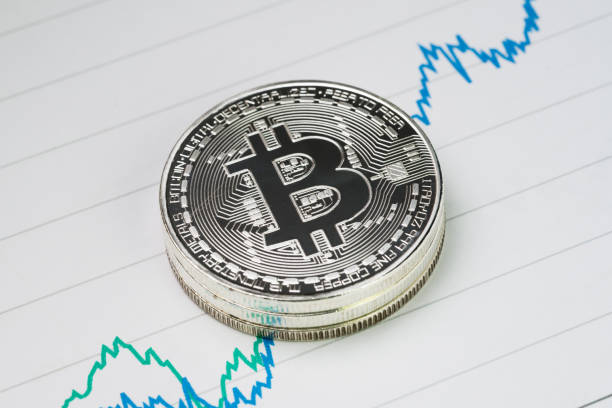 Bitcoin cryptocurrency, digital money price rise concept, stack of physical coins with B sign alphabet on rising price graph on paper Bitcoin cryptocurrency, digital money price rise concept, stack of physical coins with B sign alphabet on rising price graph on paper. initial coin offering stock pictures, royalty-free photos & images