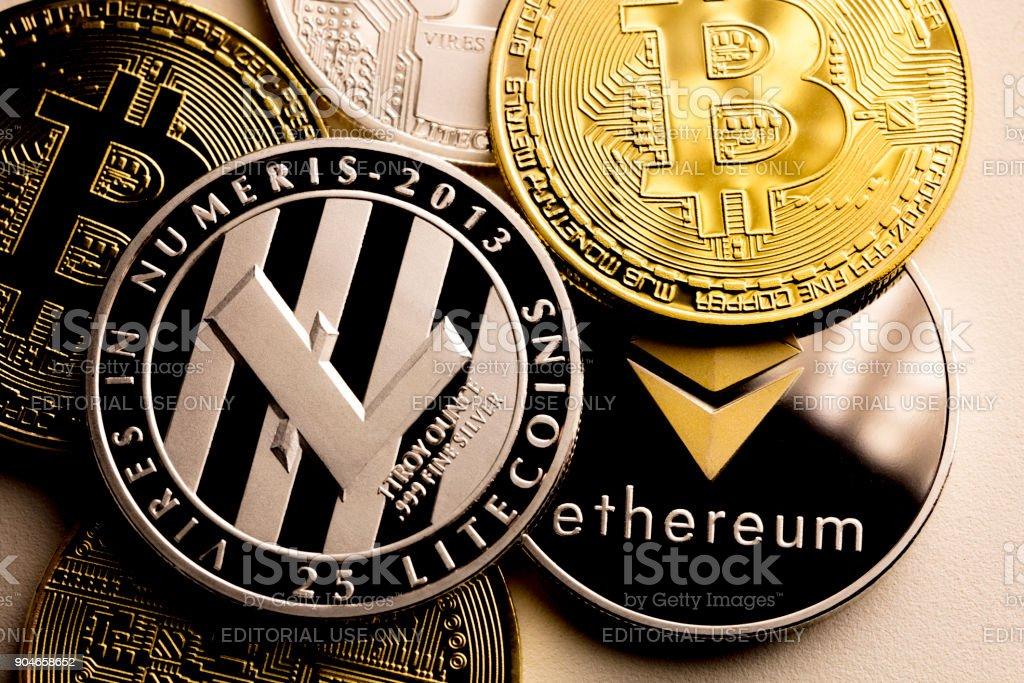 bitcoin ethereum and litecoin izmir, Turkey - January 12, 2018 Close up shot of three main cryptocurrencies; bitcoin, ethereum and litecoin in dark surface. Banking Stock Photo